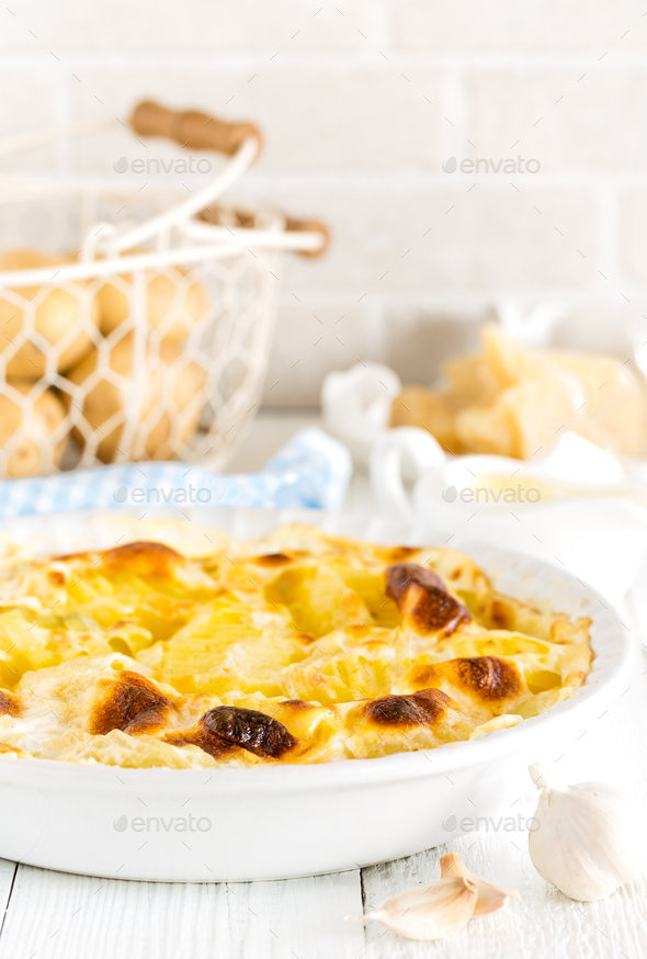 Baked potato gratin with garlic, cream and parmesan cheese - Stock Photo - Images