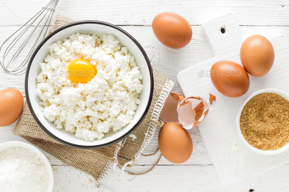 Culinary background with ingredients for cooking, cottage cheese, baking flour, sugar and eggs - Stock Photo - Images