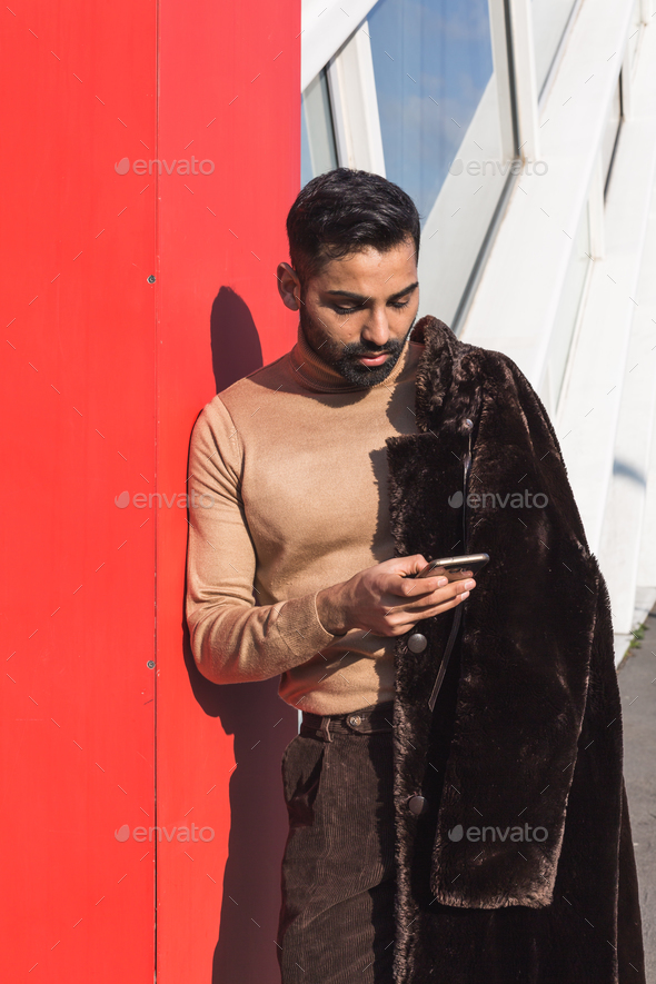 Young Indian man texting in an urban context - Stock Photo - Images