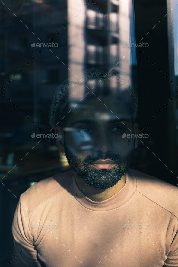 Portrait of an Indian man posing behind a glass - Stock Photo - Images