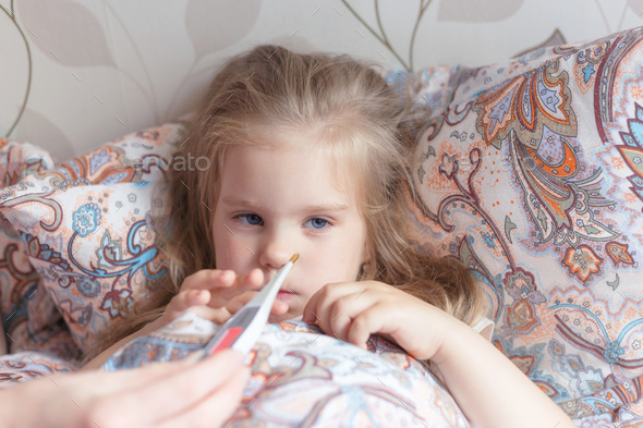 A cold little girl lies in a sad bed with fever. - Stock Photo - Images