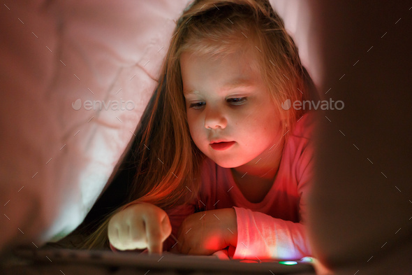 Little girl is playing on the tablet in secret from her parents at night under the blanket - Stock Photo - Images
