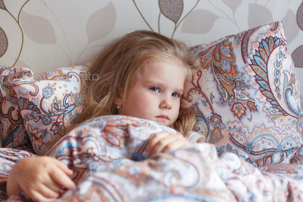 A cold little girl lies in a sad bed - Stock Photo - Images