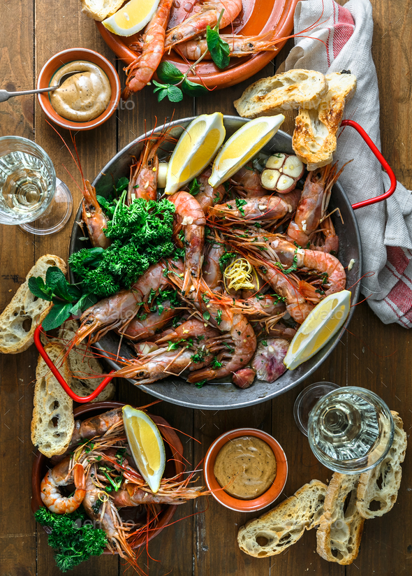 Table with many plates with shrimps, bread, lemons and wine, top view - Stock Photo - Images