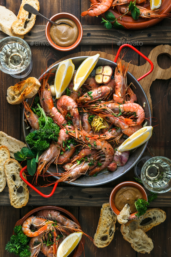 Paella pan with roasted tiger shrimps and many dishes, bread and wine - Stock Photo - Images