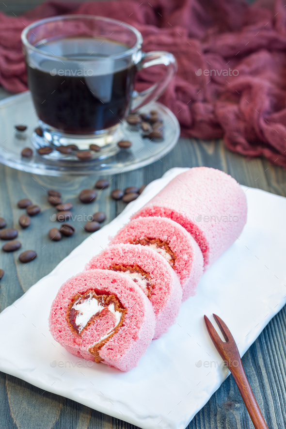 Pieces of pink swiss roll with strawberry jam and cream on a white plate, vertical - Stock Photo - Images