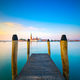 Venice lagoon, wooden pier or jetty and  poles and church on bac - PhotoDune Item for Sale