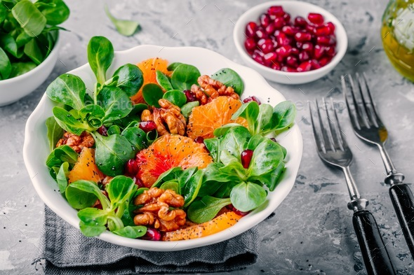 Green lettuce corn salad with blood oranges, walnuts, pomegranate and chia seeds - Stock Photo - Images