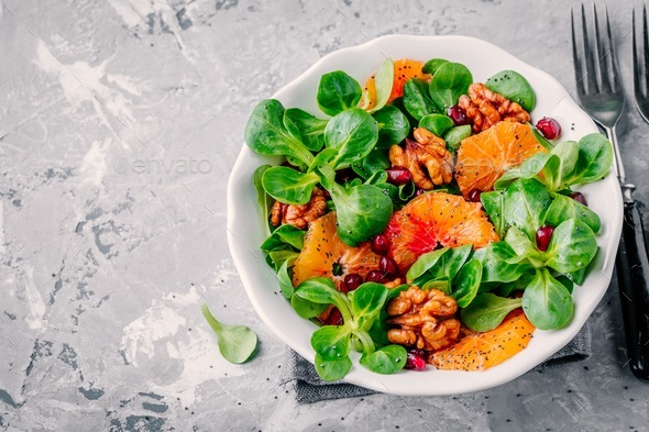 Green Lamb's lettuce corn salad with blood oranges, walnuts, pomegranate and chia seeds - Stock Photo - Images