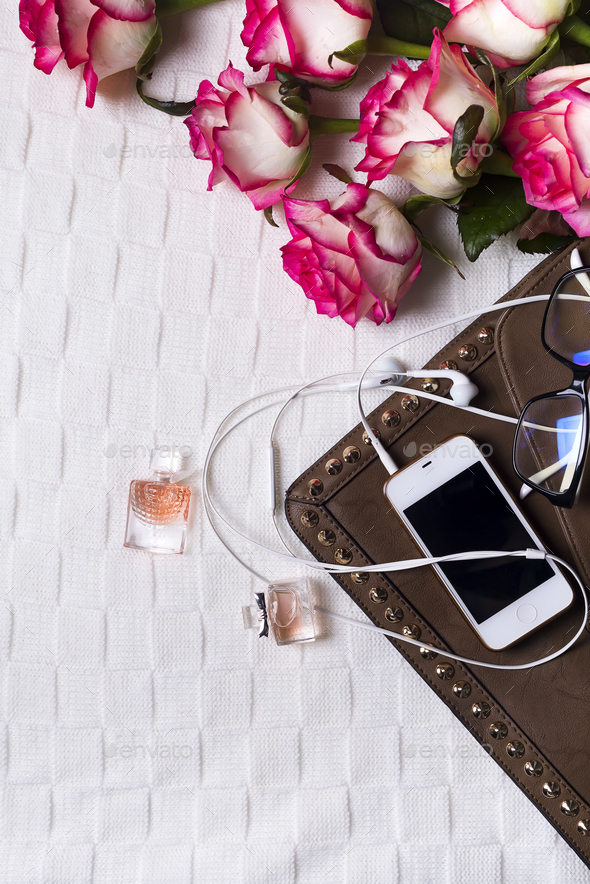 female clutch with phone, headphones and Perfume bottles with flowers - Stock Photo - Images