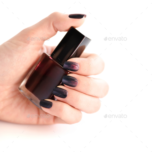 Hand of a woman with dark manicure and nail polish bottle on whi - Stock Photo - Images