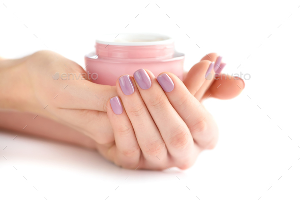 Hands of a woman with pink manicure with cream - Stock Photo - Images
