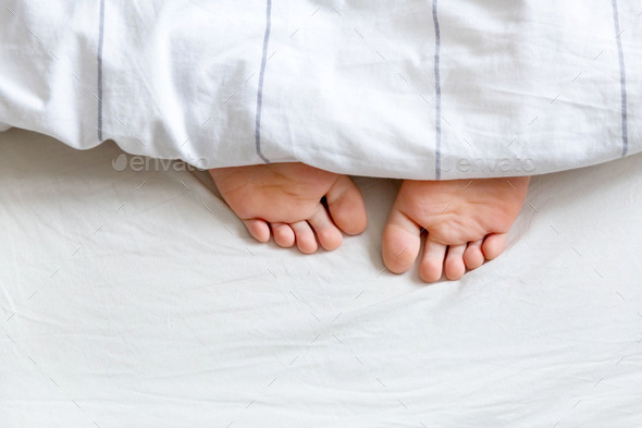 Feet under the white bedding - Stock Photo - Images