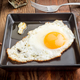 fried egg in black porcelain tray on rustic wood - PhotoDune Item for Sale