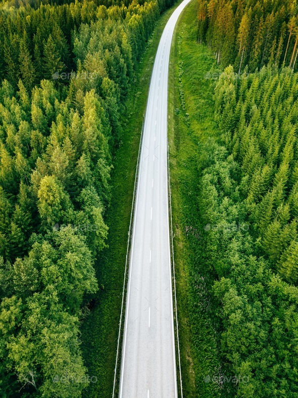 Aerial view from above of country road through the green summer forest in summer Finland. - Stock Photo - Images