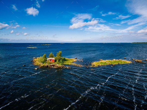 A small red cottage on an island in the blue sea on a summer day. Finland. View from above. - Stock Photo - Images