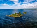 A small red cottage on an island in the blue sea on a summer day. Finland. View from above. - PhotoDune Item for Sale