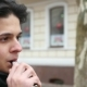 A Young Man Stands Outdoors and Smokes an E-cigarette in Winter - VideoHive Item for Sale