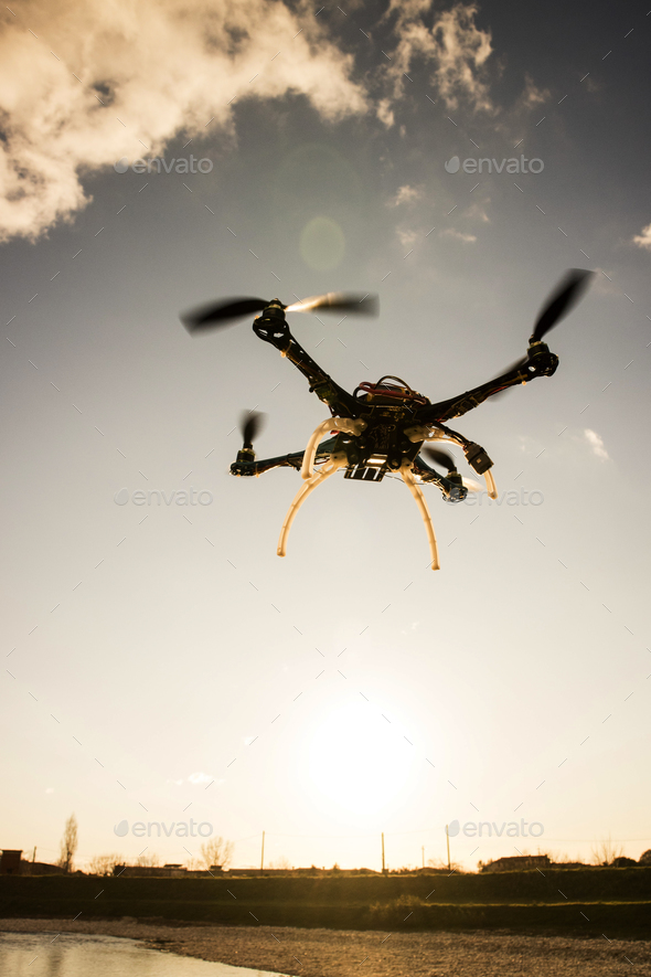Quadrocopter in flight at sunset - Stock Photo - Images