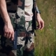 Young Military Man in Camouflage Stands in a Field with His Arms Down and Holds a Gun - VideoHive Item for Sale