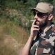 Brutal Bearded Military Male in Sunglasses Smoking Cigarette in Forest Background - VideoHive Item for Sale