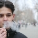 A Handsome Man Stands Outdoors and Smokes an E-cigarette in Winter - VideoHive Item for Sale