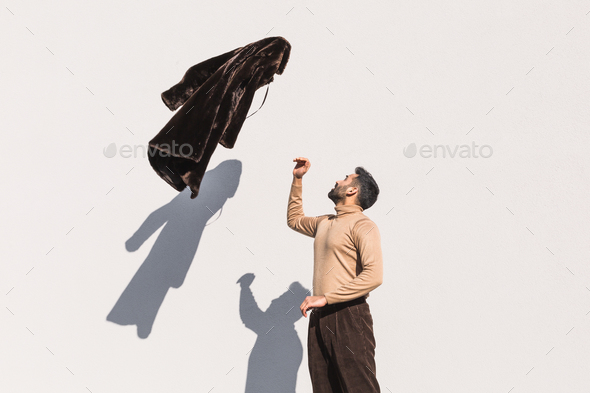 Young Indian man playing with his coat - Stock Photo - Images