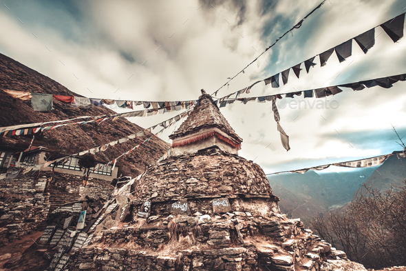 Prayer flags and buddhist stupa on trekking route - Stock Photo - Images