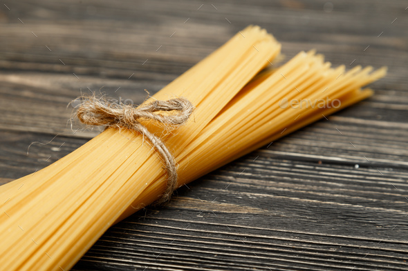 Banch of spaghetti on dark wooden table - Stock Photo - Images