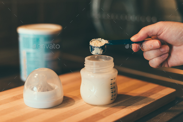 Mother making baby formula in milk bottle - Stock Photo - Images