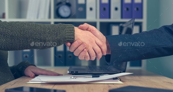 Man and woman shaking hands over business agreement - Stock Photo - Images