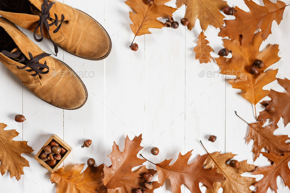 ginger fashion shoes with yellow fallen oak leaves on white wooden background - Stock Photo - Images