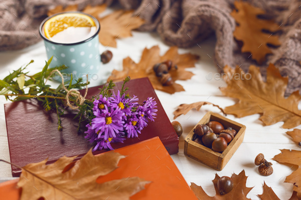 Close up view of books and cup of tea with orange. Autumn leaves, warm scarf on wooden background. - Stock Photo - Images