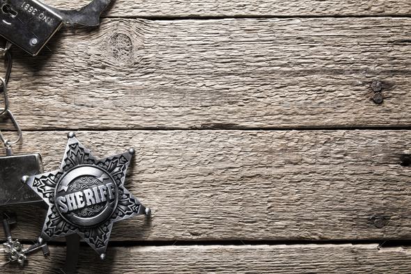 Sheriff star and handcuffs on wooden table - Stock Photo - Images