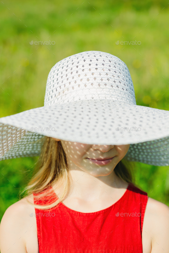 girl in red dress and white hat with large brim - Stock Photo - Images