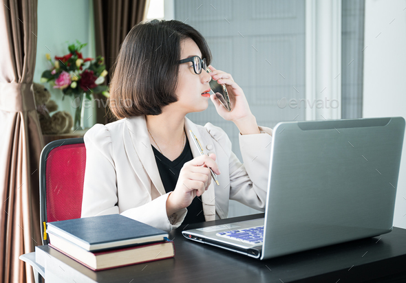 Woman working on laptop in home office - Stock Photo - Images
