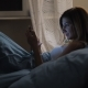 Woman In Bed Uses App On Smartphone Before Going To Sleep Looking At Pictures - VideoHive Item for Sale