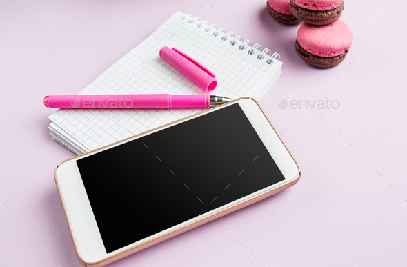 The side view on female desk. The phone and french macarons on trendy pink desk. - Stock Photo - Images