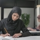 Young Beautiful Girl in a Black Hijab Writes in a Notebook, Learns, Study Arab Women in the Office - VideoHive Item for Sale