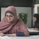 A Young Beautiful Girl in a Point and a Pink Hijab Will Write Off in Arabic Arab Women in the - VideoHive Item for Sale