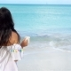 Young Woman with Hot Coffee Enjoying Beach View - VideoHive Item for Sale