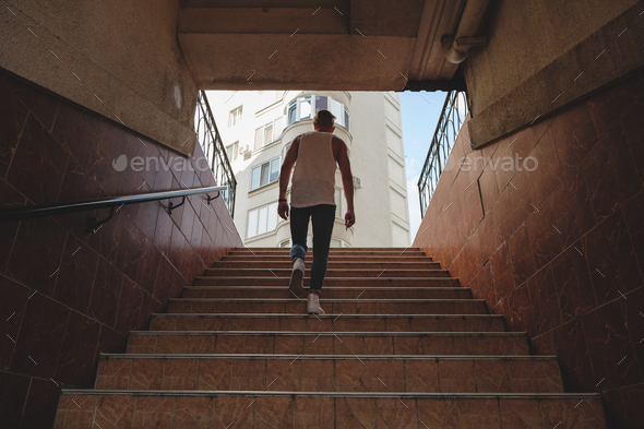 Young man climbing stairs in pedestrian subway - Stock Photo - Images