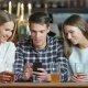 Friends Using Smartphones Sitting in the Cafe - VideoHive Item for Sale