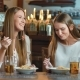 Two Smiling Young Women Having Lunch in the Restaurant - VideoHive Item for Sale
