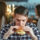 Man in a Restaurant Eating a Hamburger and Smiling - VideoHive Item for Sale