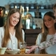 Two Young Women Getting Their Orders in Cafe - VideoHive Item for Sale