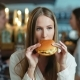 Young Happy Woman Eating Tasty Fast Food Burger in Cafe - VideoHive Item for Sale