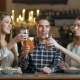 Friends Clink Glasses of Beer  on the Background of the Pub - VideoHive Item for Sale