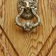 Golden door knob on a wooden door. Lion head handle - PhotoDune Item for Sale