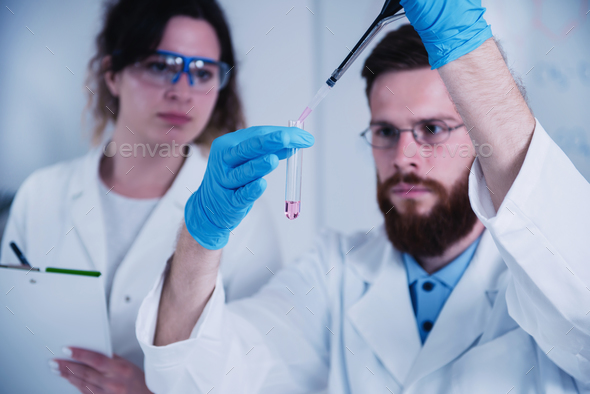 Young Male Researcher Holding Dropper And Test Tube - Stock Photo - Images